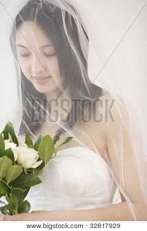 Asian bride holding flower bouquet