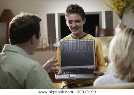 Hispanic boy showing laptop to parents