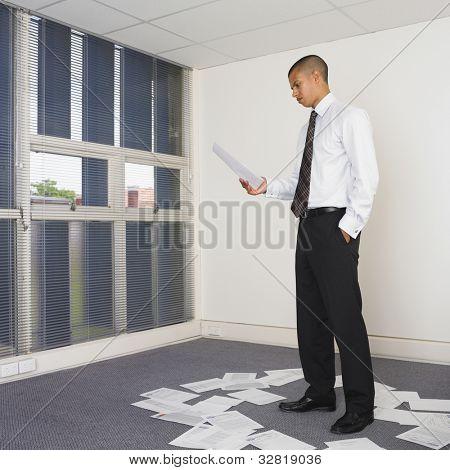 Mixed Race businessman sorting paperwork