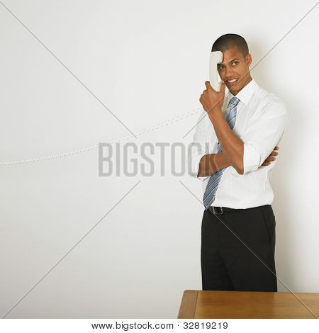 Mixed Race businessman holding telephone