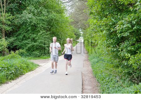 Young Couple Is Jogging In The Forest