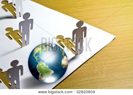 Paper cut of  people standing  with globe on wooden floor  (Elements of this image furnished by NASA)