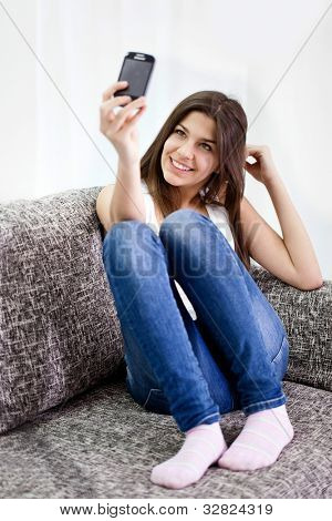 cute teenage girl taking picture of herself, smiling and looking in phone