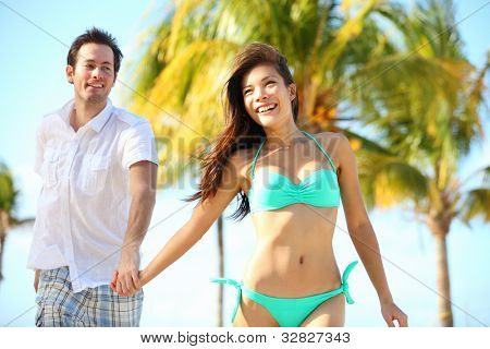 Couple having fun on beach. Happy young interracial couple running on beach during summer vacation on tropical resort. Asian woman, Caucasian man smiling happy in Varadero, Cuba