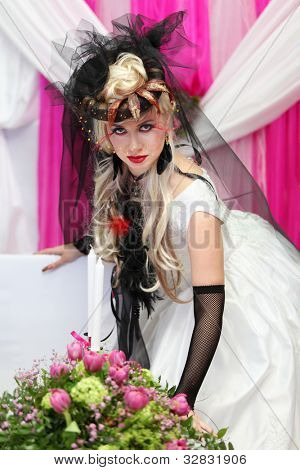 young bride wearing black net gloves and unusual hat stands near table with candle and bouquet