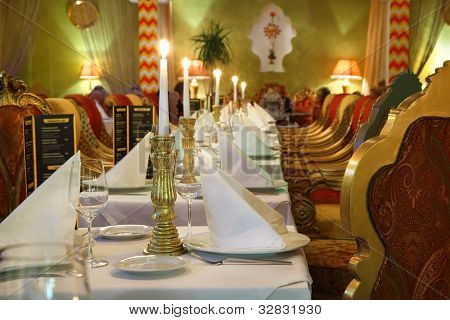 long table with serving and beautiful chairs in eastern luxury restaurant