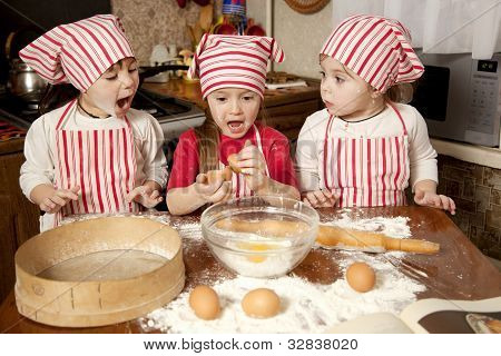Three Little Chefs Enjoying In The Kitchen Making Big Mess. Little Girls Making Bread In The Kitchen