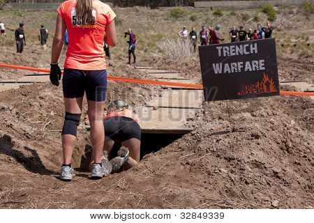POCONO MANOR, PA - APR 28: Participants crawl through trenches at the Trench Warfare obstacle at Tough Mudder on April 28, 2012 in Pocono Manor, PA. The course is designed by British Special Forces.