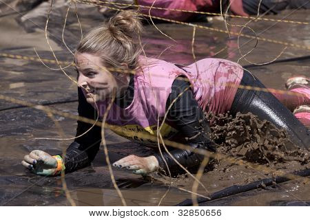 POCONO MANOR, PA - APR 29: A woman crawls through water under electrified wires at Tough Mudder on April 29, 2012 in Pocono Manor, Pennsylvania. The course is designed by British Royal troops.