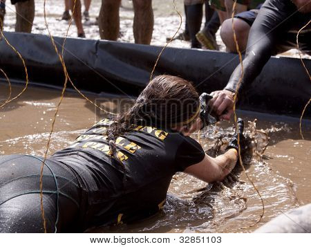 POCONO MANOR, PA - APR 28: A woman crawls through water under electrified wires at Tough Mudder event on April 28, 2012 in Pocono Manor, Pennsylvania. The course is designed by British Royal troops.