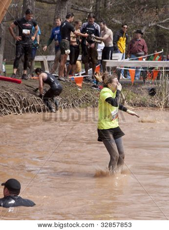 POCONO MANOR, PA - APR 28: A woman splashes into water from the Walk the Plank obstacle at Tough Mudder on April 28, 2012 in Pocono Manor, Pennsylvania. The course is designed by British Royal troops.