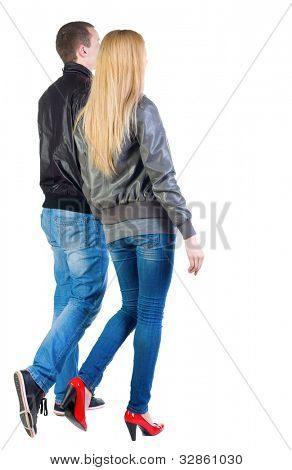 Back view of going young couple (man and woman) . walking friendly girl and guy in jacket and jeans together. Rear view people collection.  backside view of person.  Isolated over white background