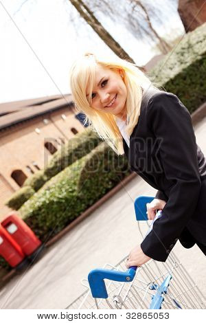 Angled view of a smiling attractive blonde woman pushing a shopping trolley across an empty carpark