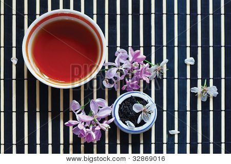 Cup of tea jar of tea leaves and cherry blossoms with lilac on bamboo table cloth