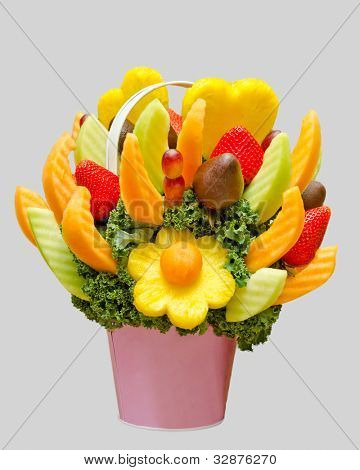an assortment of fresh fruit in a fruit basket, resembling a flower bouquet isolated on grey background