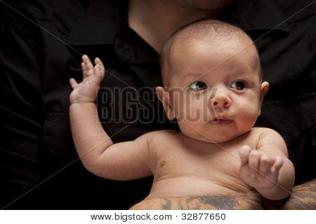 Young Father with Tattoo Holding His Mixed Race Newborn Baby Under Dramatic Lighting.