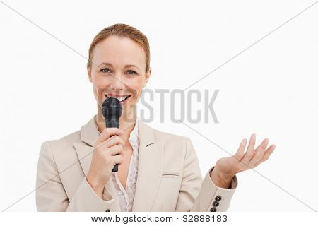 Portrait of a businesswoman speaking with a microphone against white background