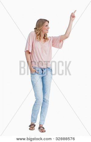 Smiling woman pointing her finger against a white background