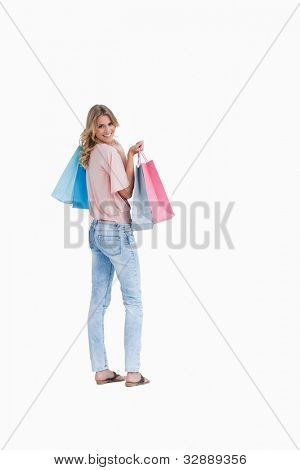 A rear view shot of a woman looking back at the camera who is carrying shopping bags against a white background
