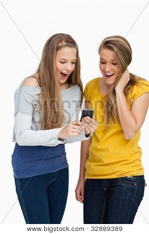 Two surprised students looking a cellphone screen against white background
