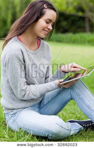 Young woman sitting on the grass in a parkland while holding a tablet computer