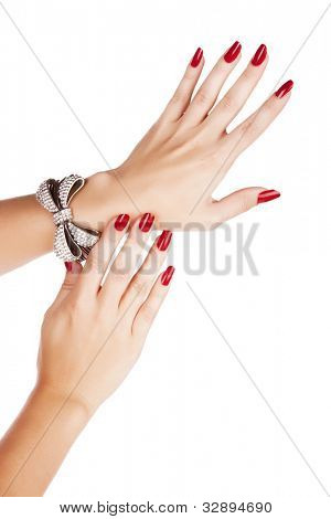 closeup hands of young woman with red manicure polished nails wearing diamante bow bracelet