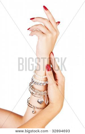 closeup hands of young woman with red manicure polished nails wearing many silver bangles and pearl bracelets
