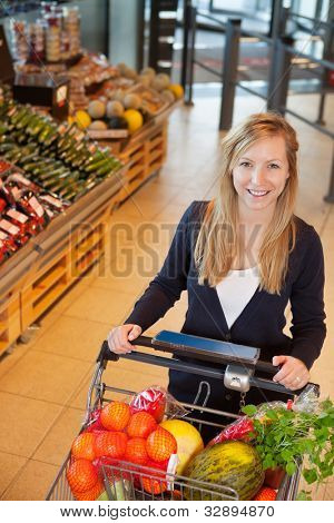 Smiling woman looking at camera while holding shopping cart in store