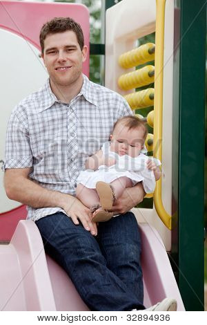 Father Sitting On Slide With His Adorable Daughter.