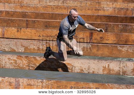 POCONO MANOR, PA -APR 29: A man falling into water after attempt to walk across a narrow beam at Tough Mudder on April 29, 2012 in Pocono Manor, Pennsylvania. British Royal troops designed the course.