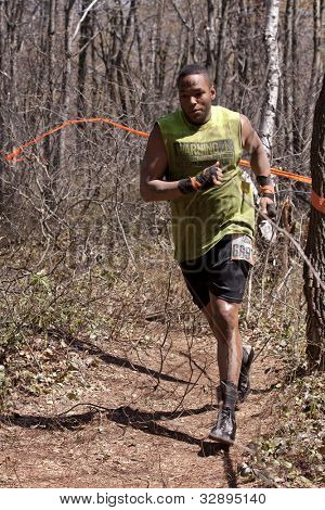 POCONO MANOR, PA - APR 29: A man runs on a trail through the woods at Tough Mudder on April 29, 2012 in Pocono Manor, Pennsylvania. The course is designed by British Royal troops.