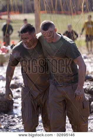 POCONO MANOR, PA - APR 29: Muddy participants come through an obstacle with electrified wires at Tough Mudder on April 29, 2012 in Pocono Manor, Pennsylvania. British Royal troops designed the course.
