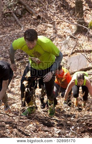 POCONO MANOR, PA - APR 28: Participants run up a steep hill through the woods at Tough Mudder on April 28, 2012 in Pocono Manor, Pennsylvania. The course is designed by British Royal troops.