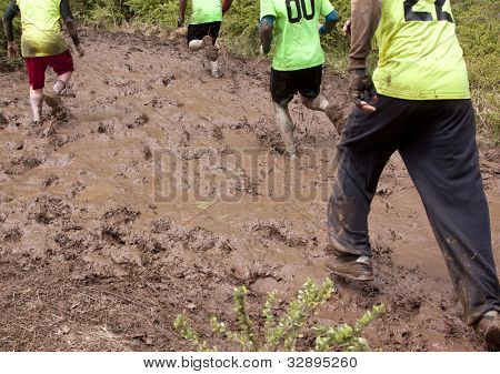 POCONO MANOR, PA - APR 28: Participants walk through large areas of deep mud at Tough Mudder on April 28, 2012 in Pocono Manor, Pennsylvania. The course is designed by British Royal troops.