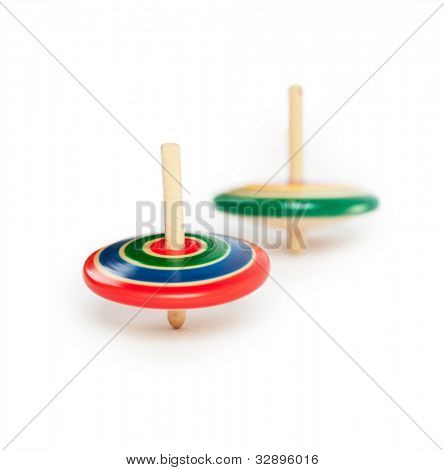 two wooden top, spinning. Isolated on white.