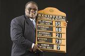 stock photo of preacher  - African man holding hymn board - JPG
