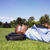 stock photo of solemn  - African businessman laying in grass - JPG