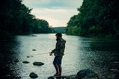 Fishing Became A Popular Recreational Activity. Handsome Fisherman Fishing In A River With A Fishing poster