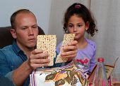 Jewish Family Celebrating Passover.jewish Man Blessing On Matzah As They Celebrate Seder. The Feast  poster