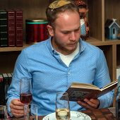 Jewish Family Celebrating Passover.jewish Man Reads From The Haggadah As They Celebrate Seder. The F poster