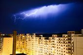 stock photo of lightning-rod  - lightning arching above a city during a thunderstorm with light comming down from the sky - JPG