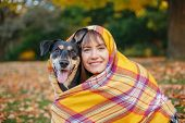 Woman Wrapped In Woollen Blanket With Dog In Autumn Fall Park. Beautiful Happy Young Caucasian Woman poster