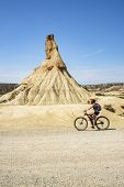 Woman Rides On Wonderful Mountain Biking Trails In Bardenas Reales. Natural Park. Biosphere Reserve  poster