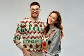 christmas, people and holidays concept - portrait of happy couple at ugly sweater party poster