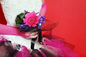 stock photo of jupe  - hands in pink mesh gloves of bride wearing in unusual dress hold small bouquet - JPG