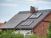 Large Solar Panels On Roof Of House. Horizontal Orientation, Blue Sky, Gray Panels On Brown Roof. poster