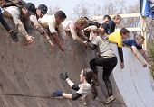 POCONO MANOR, PA - APR 28: Men help other participants up the Everest obstacle at Tough Mudder on Ap