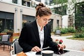 Business Lady Sitting On Veranda In Coffee Shop While Working By Digital Social Media Project On Tab poster