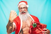 Happy Fit Santa Claus Holding Christmas Present - Hipster Senior Having Fun Celebrating X-mas Holida poster