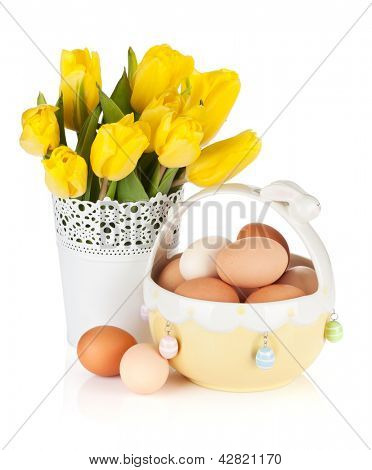 Fresh yellow tulips and eggs in bowl. Isolated on white background